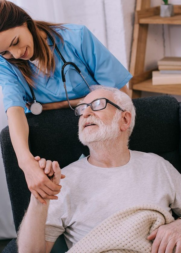 nurse-supporting-and-holding-hand-of-smiling-senio-3MFW4J7